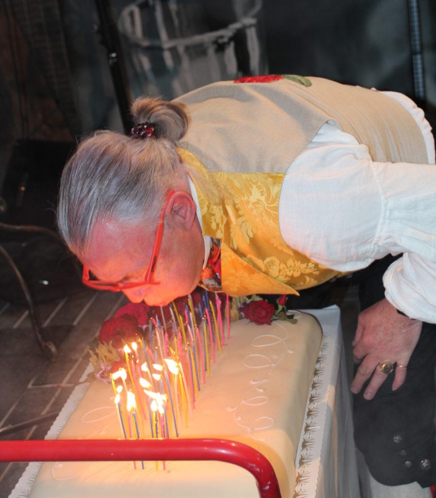 Finn Schjøll blåser ut lysene på bursdagskaken.